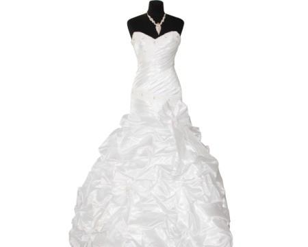 White wedding dress on black dress form against white background