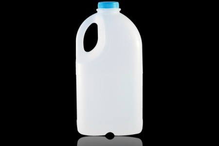 A single plastic 1/2 gallon milk jug against a black background.