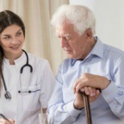 Female community health nurse speaks with elderly male patient who is seated holding a cane.