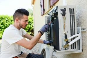 Man repairing an exterior home  air conditioning unit