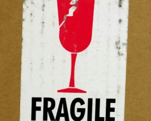 Red image of broken glass and the word FRAGILE in black on a white label against a cardboard box background.