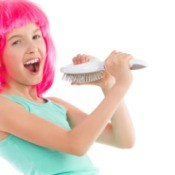 Young girl wearing hot pink wig singing into hairbrush against a white background