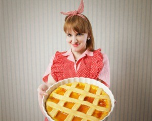 Woman in red checked apron holding homemade lattice crust pie