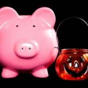 A piggybank next to a Halloween pumpkin candle holder.