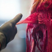 Hair being dyed a bright red color.