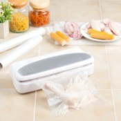 Vacuum sealer on tile counter with vacuum bag containing a chicken thigh.  Multiple other meat items such as hot dogs are off to the side and two rolls of unused vacuum bags are in the background.