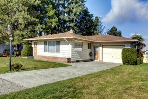A small one story home with a long concrete driveway and lawn
