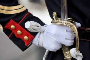 Close up of soldier in dress uniforms gloved hand holding sheathed sword