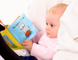 "Baby in pink sweater in a car seat ""reading"" a fabric book"