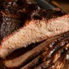 Close up of beef brisket partially sliced on a wooden cutting board