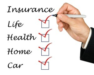 "Male hand holding pen against a white background with the word Insurance and under it checkboxes for ""Life"", ""Health"", Home"", ""Car"" all checked off in red."