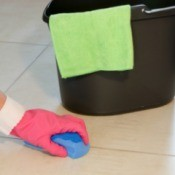 Hand wearing pink glove scrubbing white vinyl floor with blue sponge.  Black bucket with green cloth in the background
