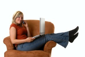 Woman with laptop and phone sitting across a rust colored armchair.