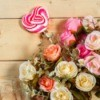 Bouquet of roses with a decorative candy striped red heart on a stick against wooden background