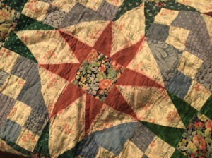 Closeup of quilt showing where red color bled into surrounding light colored fabric