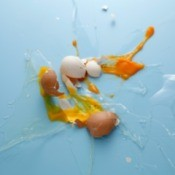 Splattered brown and white eggs against blue background