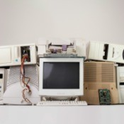 Several old tube style computer monitors and 1990s era CPUs stacked against a white background