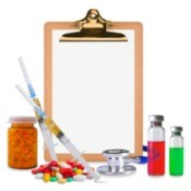 Medical supplies surrounding a clipboard with blank page