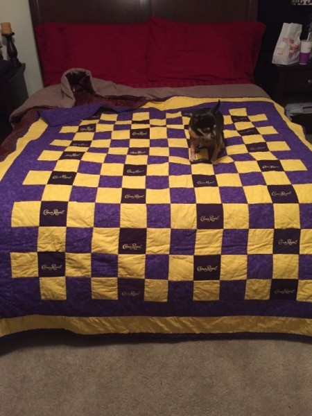 Crown Royal quilt on bed with puppy