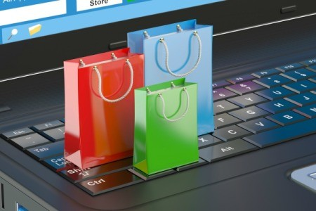 Three tiny gift bags standing on a laptop keyboard