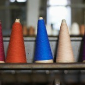 Five thread cones with different colors of thread lined up on a shelf