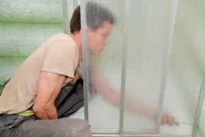 Man working on an old shower door with metal frame