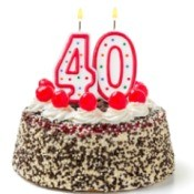 Burning candles shaped like the number 40 on a cake against a white background