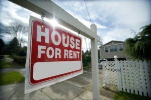 Close up of a House For Rent sign with home in the background