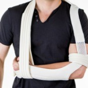 Man's arm in complicated shoulder sling against white background