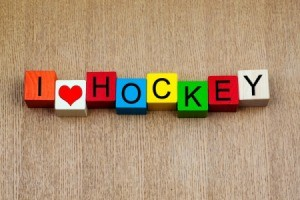 "Blocks spelling out ""I [heart] HOCKEY"" against wood background"