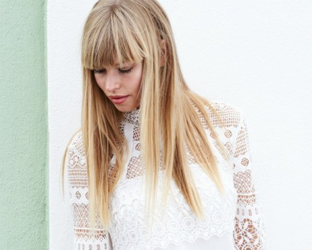 Woman in white lace shirt gazing down