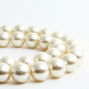 Strands of pearl necklace against a white background