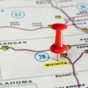 Close out of map with red push pin on Wichita, Kansas.  The word Wichita is highlighted.