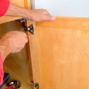 Close up of a man's hands attaching a cabinet door to the cabinet hinge using a screwdriver
