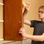 Man sanding kitchen cabinet door