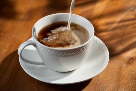 Liquid creamer being poured into white coffee cup on a table