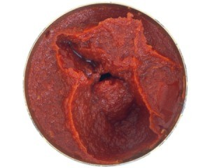 Top view of tomato paste can with a spoonful of paste removed against a white background