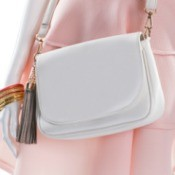 Close up of a white leather Purse on a mannequin wearing a pink dress.