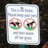 "Close up of sign reading, ""This is our home  Please keep your pets and their waste off our grass."""