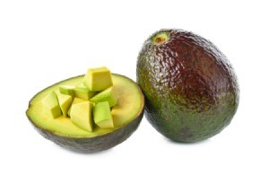 A whole avocado, half avocado, and some diced avocado against a white background