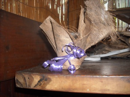 fiber wrapped glass with purple ribbon tied around