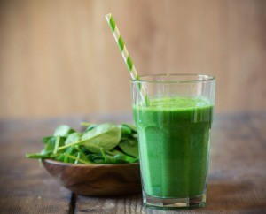 Green smoothie next to a bowl of fresh spinach leaves on a wooden table