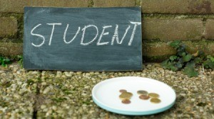 Chalkboard with the word student written on it leaning against a wall behind a plate containing a few coins.
