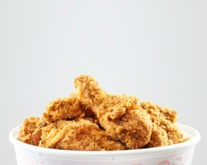 Fried chicken in paper bucket against a white background