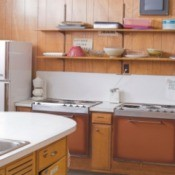 Basic 1970s era kitchen with old appliances and plats on a shelve along the wall