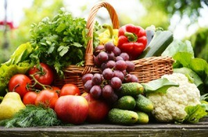 Variety of garden vegetables and fruits in and surrounding a basket on a table.