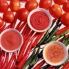 Bowls of tomato sauce, tomato sauce, and tomato puree' laying on top of fresh whole tomatoes and peppers on a white backgound