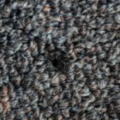 Close up of a cigarette burn on dark carpet