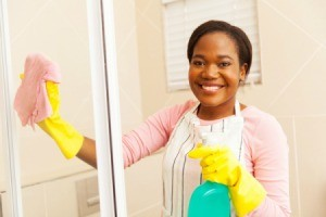 Smiling woman cleaning a shower door