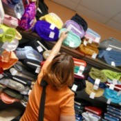 Woman checking prices on rolls of plush and fleece fabrics
